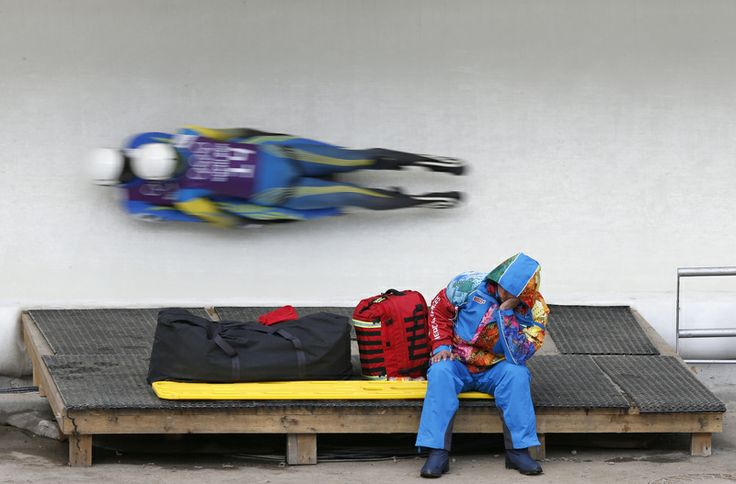 10.02.2014 Ukraine's Oleksandr Obolonchyk and Roman Zakharkiv speed down the track as a staff member rests during a men's doubles luge training session...