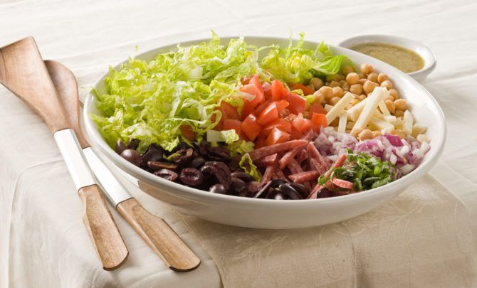 A filling salad of lettuce, garbanzo beans, olives, tomato, onion, provolone, salami and basil, dressed with vinaigrette.