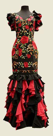 Traje de flamenca confeccionado con cuerpo de mantón de manila bordado en seda en tonos negro, rojo y oro.    La falda es de crespón combinada en rojo y negro con volantes irregulares en vertical acabados en pico, que aportan gran vistosidad al vuelo durante el baile.
