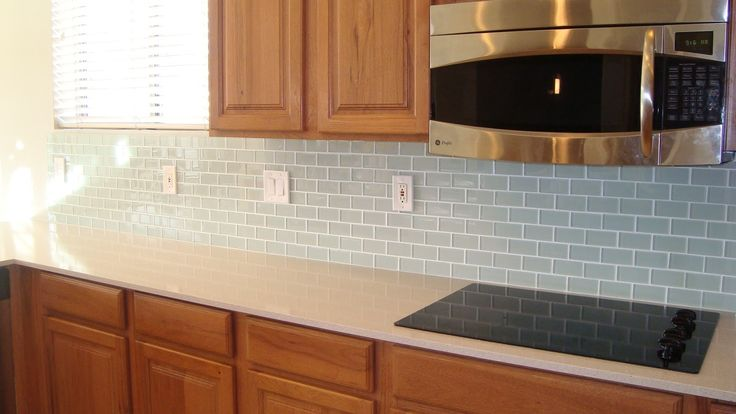 Blue glass backsplash tile with oak cabinets and white Backsplash ideas quartz countertops