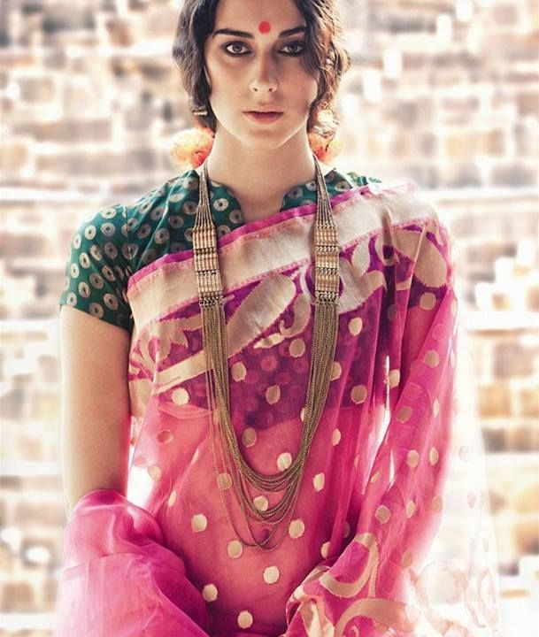 This Pink Banaras Net saree is from Ekaya Boutique, New Delhi. Saree is paired with high neck contrast green blouse. Accessorised with antique Chandraharam amd gold buttas.