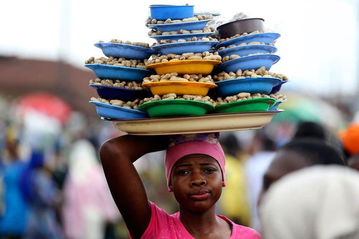 A girl hawks groundnuts along a road in Nigeria's southwestern city of Osogbo. | (REUTERS/Akintunde Akinleye)