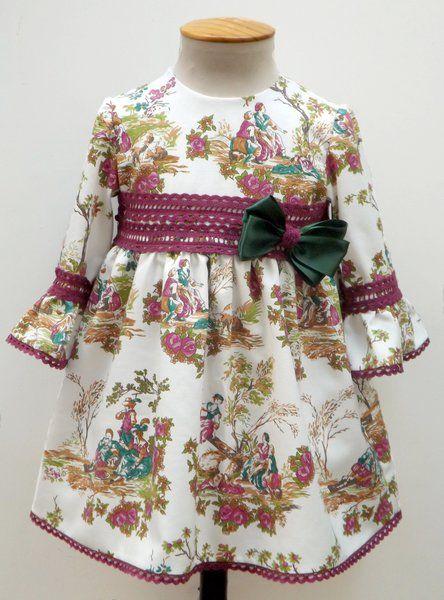 Vestido para bebe niña de toilé en tonos buganvilla y manga francesa, adornado con encaje de bolillos y un lazo verde a juego. Talle alto