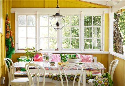 A dining room in fun summer colors on the porch of a summer cottage in Sörmland, Sweden.