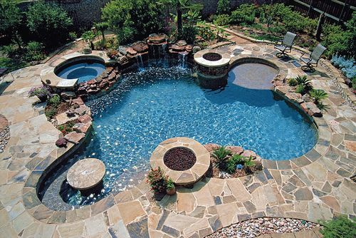 This has a Jacuzzi, a water fall, a fire pit, a shallow flat entry, and a round table with bench seating! This is the perfect pool!