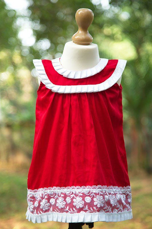 Red frock with lace border on the neck and yoke and hem edged with pleated ribbon. Available for newborns and above up to one year.