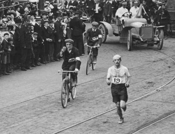 Dorando Pietri with a commanding lead in the marathon, approaching the Olympic stadium in London, 1908.  Moments later he collapsed from exhaustion and failed to finish without assistance.  He was disqualified and Johnny Hayes of the USA who finished 2nd, would be declared the winner.