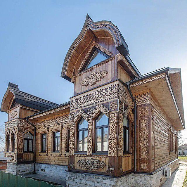 Деревянный дом терем с изобилием резьбы на фасаде