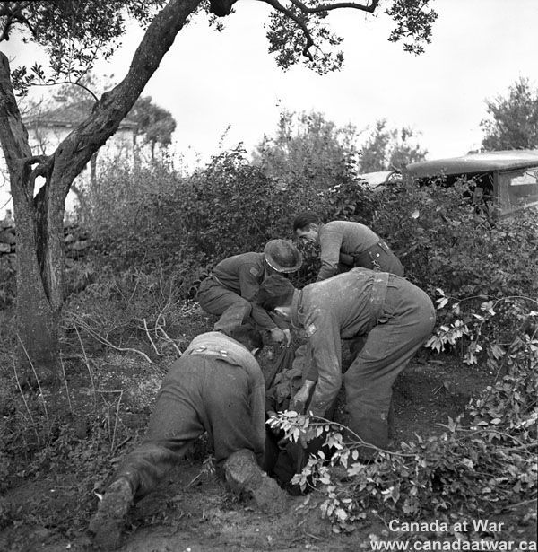The Moro Valley - Burial service of Canadian soldier killed by shell-fire. San Leonardo di Ortona, Italy. December 10, 1943.
