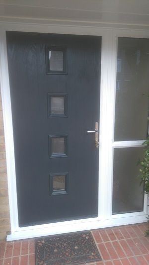 Britannia Windows - West Sussex Grey Composite Door with 4-square glass panels and chrome furnishings. White Frames with side panel.