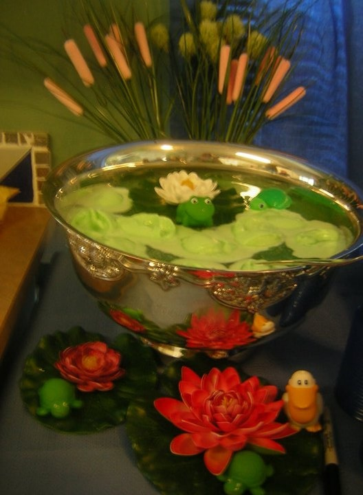 Pond punch. Traditional punch recipe with ginger ale, pineapple juice, and the blue Hawaiian punch -add lime sherbet right before serving. Floating lily pads from Lowe's and frogs from Babies R Us.