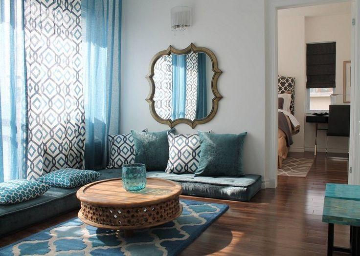 décor oriental dans un salon cosy, tapis bleu, canapé d'angle en velours et coussins décoratifs assortis