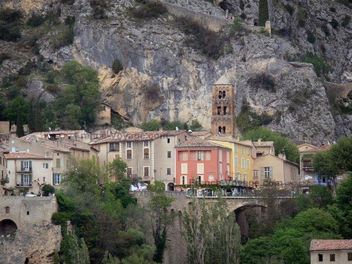 Paysages des Alpes-de-Haute-Provence : Village de Moustiers-Sainte-Marie : clocher de l'église Notre-Dame-de-l'Assomption, maisons, falaise (paroi rocheuse) et chemin de croix menant à la chapelle Notre-Dame-de-Beauvoir ; dans le Parc Naturel Régional du Verdon