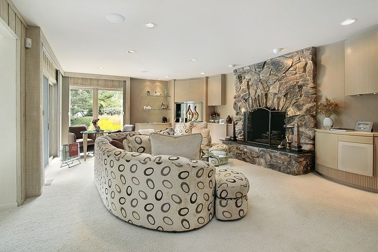 Casual living room with large stone fireplace and patterned sofa.