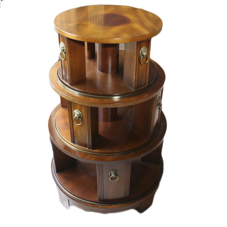 """A John Widdicomb Regency inspired revolving bookcase. This hardwood bookshelf features three tiered shelves, of which only the top two revolve. It is stained a rich mahogany color and it features brass tone lion head pulls. It is marked on the underside """"Mario Buatta for John Widdicomb""""."""