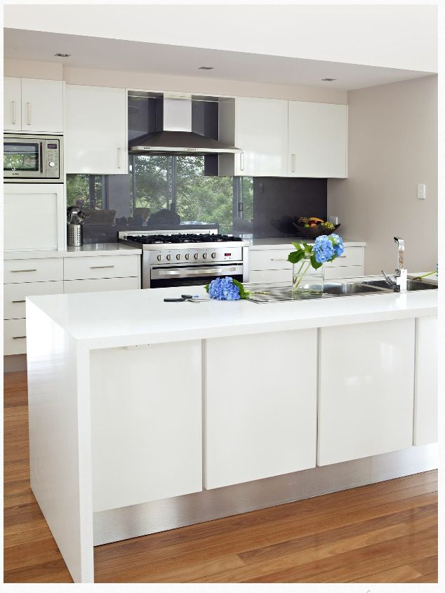 a charcoal splash back, white kitchen with timber floors