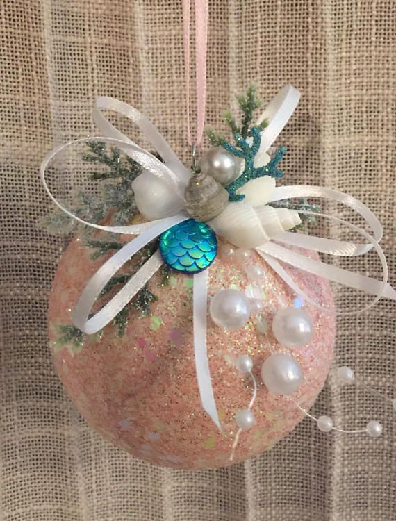 Pink sparkling ornament with coastal embellishments and mermaid scales.