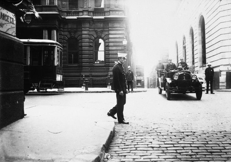 Photographie de pompiers à bord d'une autopompe sur la rue Saint-Pierre en direction nord, au coin de la rue St-Jacques Ouest. On y aperçoit un policier traversant la rue et l'avant d'un tramway. Appareil incendie . - 1927 Archives de la VIlle de Montréal, VM094-Y-1-17-D0437