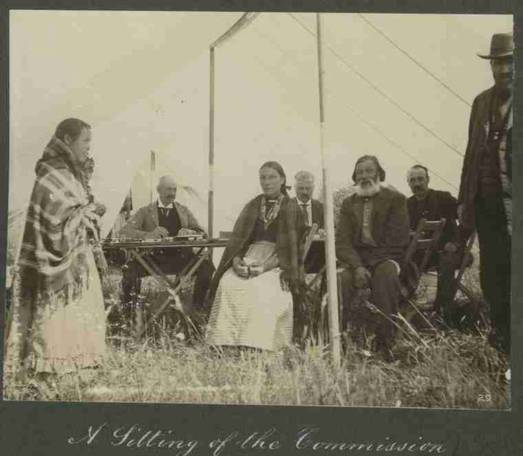 A photograph of the Half-Breed Commissioners sitting in their mess tent with Metis men and women during their visit to Devil's Lake near Sandy Lake reserve, 1900. Royal Commission investigating and adjudicating Metis claims.  The Commission was to enumerate and issue scrip to the Metis who qualified in the district of Saskatchewan and a small part of Manitoba. Their work lasted from May 16 to December 6 1900.