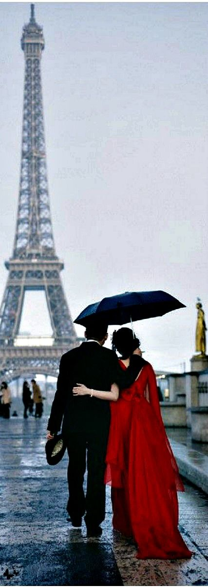 Paris in the Spring, rainy day stroll under umbrella, girl in long red dress, Eiffel tower in the background.