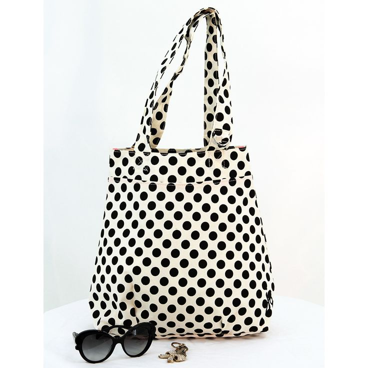 Polka dot is the new black! This classic Cream and Black Polka Dot tote has a magnetic snap closure at the top, an EVA-lined interior with pink piping, and an inside pink zippered pocket with grosgrai