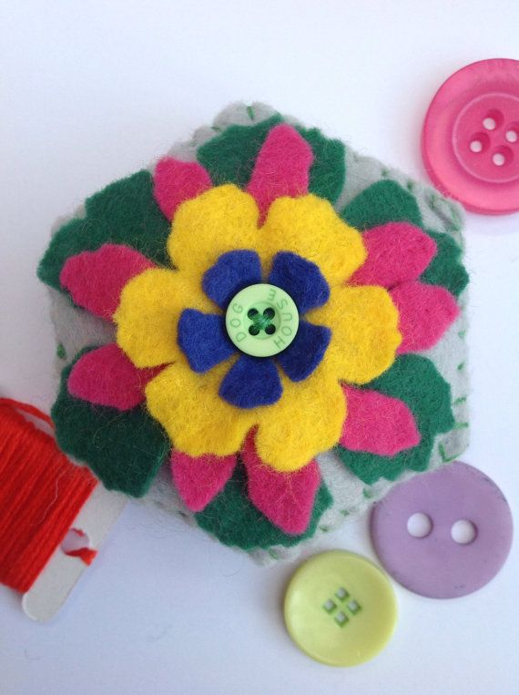 This is a hand sewn, hexagon shaped, felt pincushion with a flower motif and button detail. It can be used as a pincushion or a decoration to brighten up any home. This item measures approximately 8 cm x 8 cm and is made from high quality wool felt. Flower is cut using a Tim Holtz die, layering complementary colours of green, pink, yellow and blue to make the a beautiful flower motif, finished with a green button at the centre. The bottom layer is stitch on to the base cushion, while the…