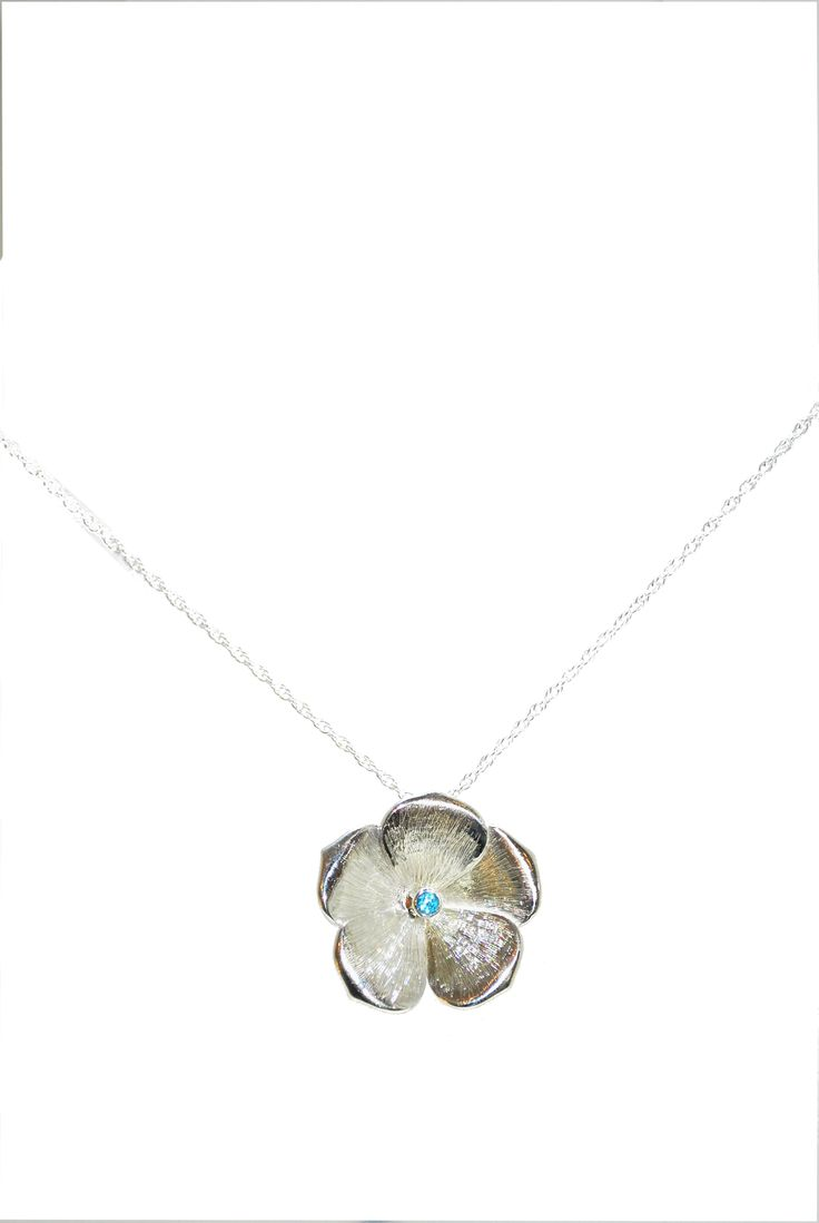 This silver pendant features detailed petals that engulf a striking blue topaz. By Adrew O'Dell #silver #contemporary #boutique #London  #designer #jewellery  #NudeJewellery