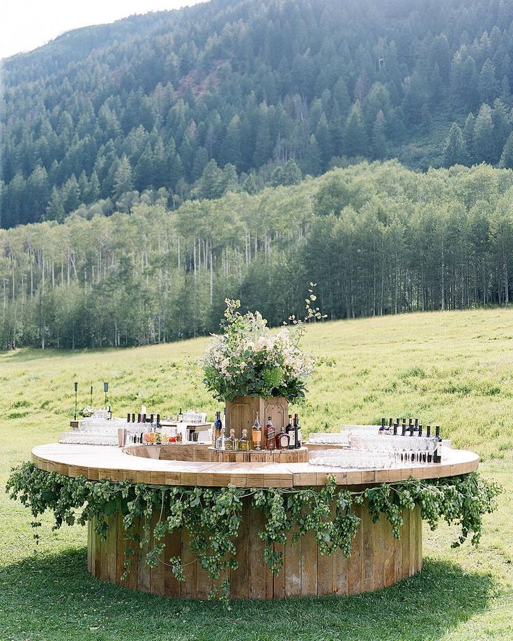 Gorgeous custom round wood bar draped with greenery by Easton Events