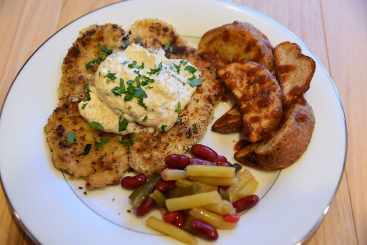 Easy Schnitzel recipe - Pounded pork with a beer based batter and panko breadcrumbs. Fried to golden perfection, topped with a dill sour cream sauce.