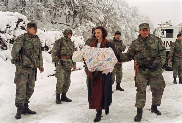A refugee woman from the Srebrenica area carrying a child arrives 29 March 1993 in Tuzla escorted by Bosnian soldiers The Moslem population of...