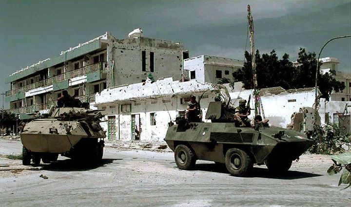 An American Cadillac Gage Light Armored Reconnaissance Vehicle and Italian Fiat-OTO Melara Type 6614 Armored Personnel Carrier guard an intersection during the Somali Civil War (1993)