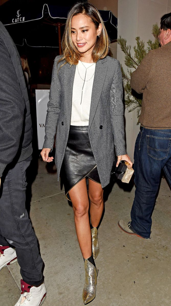 Jamie Chung in a black leather miniskirt, white top, long gray blazer and gold Aska booties - click through to see more celebrity winter outfits