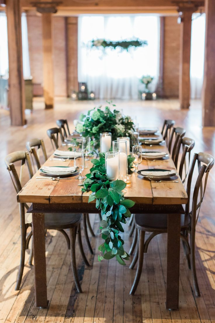 {{Winter wedding farm table with southern smilax garland and pillar candles at Bridgeport Art Center in Chicago.}} Photography by Tiffaney Child's Photography http://tiffaneychilds.com/    Flowers by Pollen, pollenfloraldesign.com