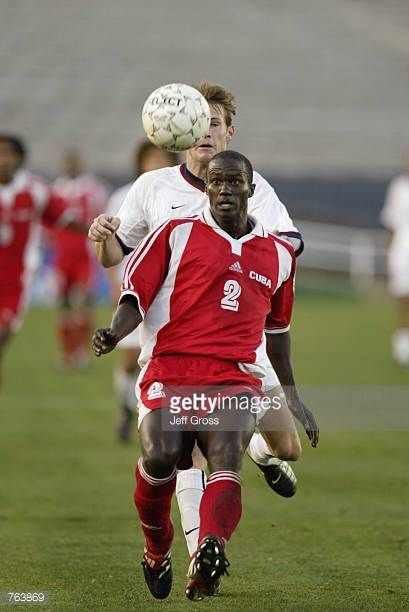 Alexander Driggs of Cuba battles for possession of the ball under pressure from Brian McBride of the USA during the first round of the CONCACAF Gold...