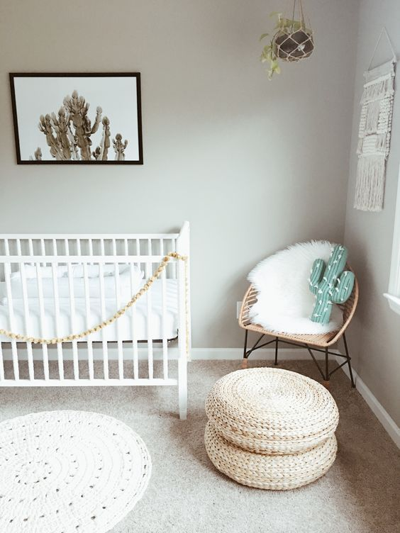 Southwestern nursery design with a a gray, white, tan, and green color palette featuring cactus wall art, a cactus pillow, rattan chair with a sheepskin throw and rattan poufs - Modern Nursery Ideas & Decor