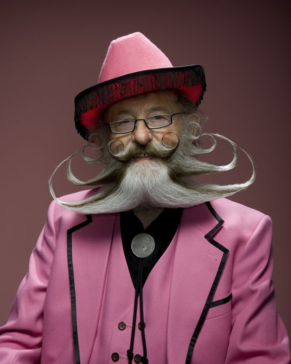 As if the beard isn't enough he wears a pink suit and hat!