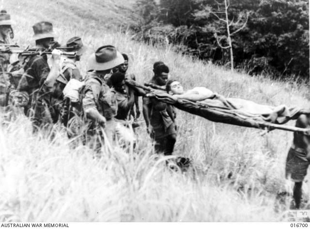 A wounded soldier is carried by local natives past a Shaggy Ridge patrol.    A shot from the Department of Information film 'Jungle Patrol'.   Finisterre Range, New Guinea - January, 1944.