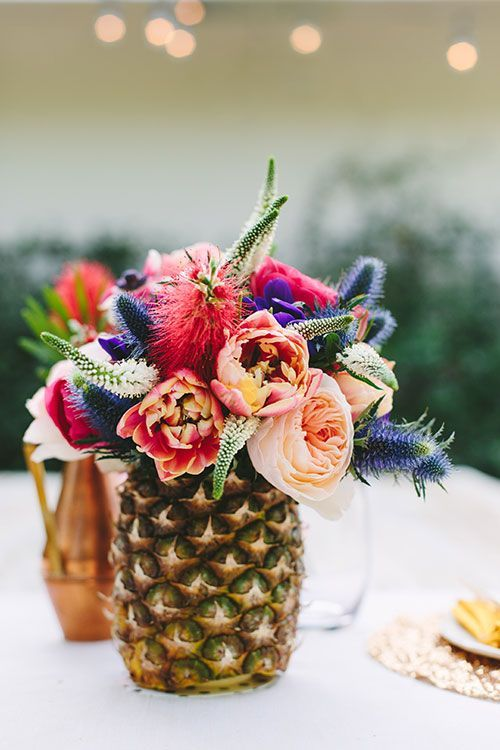 Cut out the center of a fresh pineapple and add tropical flowers for a nice and fragrant floral centerpiece. | Photo Credit: Mary Costa Photography