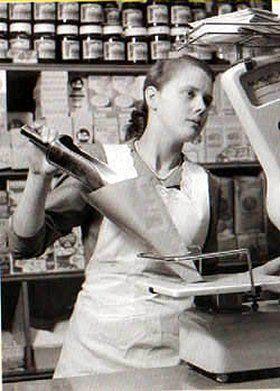 Vriendelijk en beleefd winkelmeisje, bij de kruidenier waar alles achter een toonbank nog voor de klant werd afgewogen. Rond 1960.