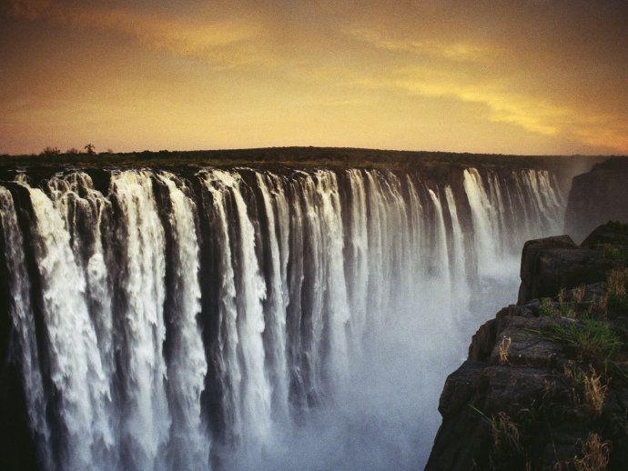 """Victoria Falls - Zambia e Zimbabwe Na fronteira entre Zâmbia e Zimbabwe, nade num horizonte de água inifinito, à beira de um penhasco, na chamada """"piscina do diabo"""", nas Cataratas de Victoria. No século XIX, a tribo Kokolo chamava as Cataratas de """"Mosi-oa-Tunya"""", a fumaça que ruge. Essa ainda é uma descrição perfeita da impressionante queda d'água que se lança sobre rochedos de basalto ao longo da fronteira com a Zâmbia. Perto dali há uma aldeia do povo Mukuni e um parque com girafas…"""