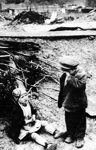 World War II, Great Patriotic War. Russian children stayed aban-doned at the ruins of their house. The Nazi destroyed it and put their parents in prison. Russia, 1942.