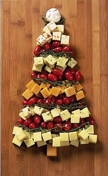 A Christmas tree made out of cheese cubes and cherry tomatoes -very fun Holiday themed appetizer!