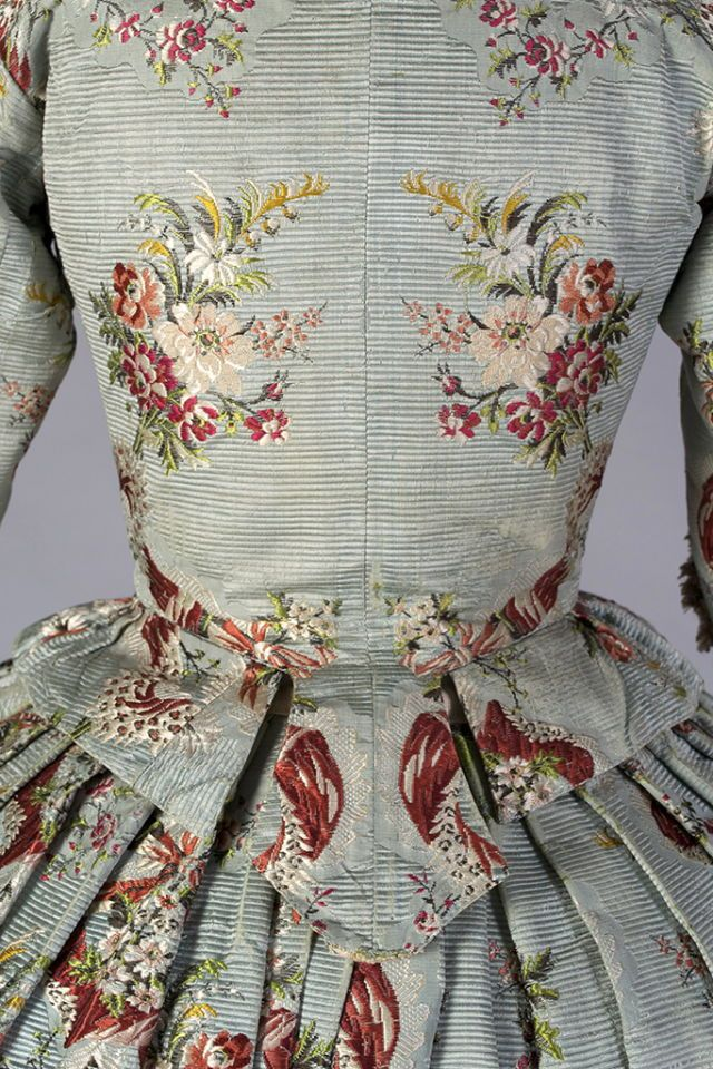 This matching bodice and skirt dates to around 1765. The textile is a magnificent brocaded silk. The close-up photographs give a sense of the texture of the ribbed silk and the brocaded floral patterns. The stomacher with the peach bows is a reproduction, which the Museum Director Jean Druesedow created from silk which she carefully dyed to match and ribbons. Detail 5 Kent State University Costume Museum