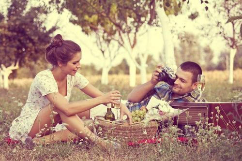 .Sweetly taking a picture of his love on a picnic-  romantic