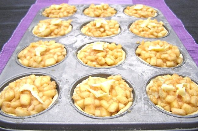 Apfeltörtchen im Muffinblech 250 g Mehl 50 g Puderzucker 125 g Butter (nicht ganz kalt, aber auch nicht Zimmertemperatur...) 2 gehäufte Esslöffel Quark 1 Ei 1 TL Essig  3-5 säuerliche Äpfel  1 Zitrone 3 EL Rum (evtl. weglassen...) 2-3 EL Zucker 1-2 TL Zimt (nach Geschmack) 1 geh. EL Stärke  1 EL Butter