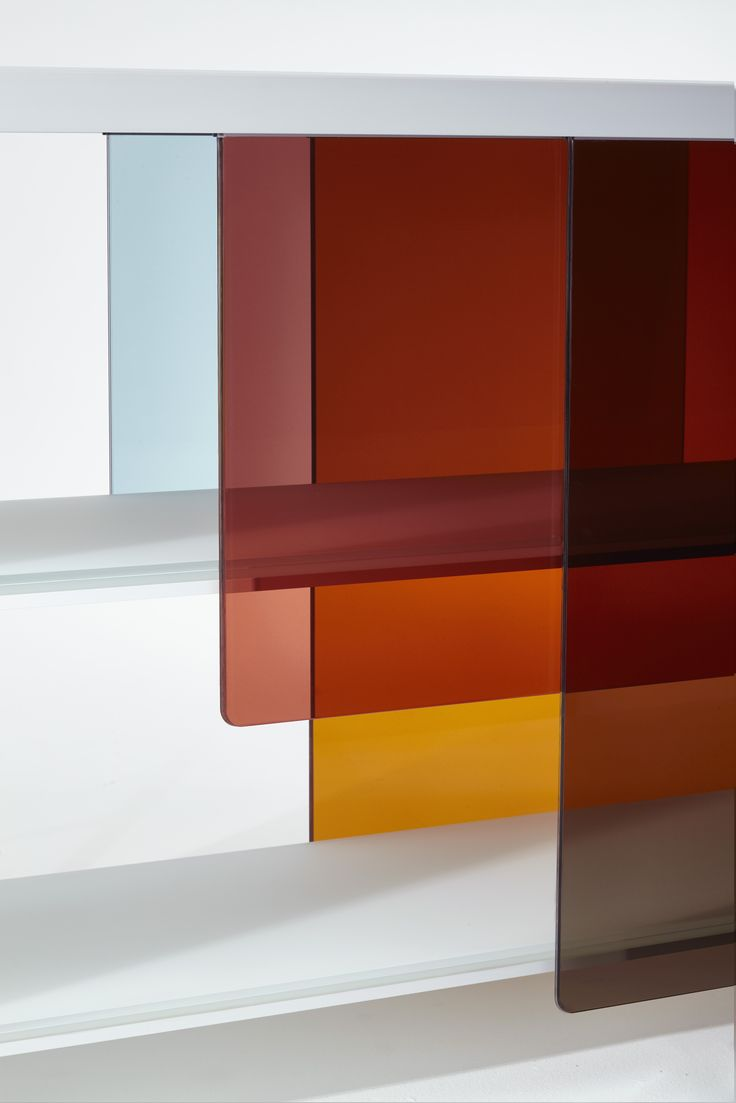 LAYERS design Nendo | Bookshelves in white matt extralight lacquered glass laminated and glued. The shelves are partially obscured by sliding doors suspended from the top, made of transparent glass with special colors which, by overlapping, create constantly changing chromatic imagery. Two versions are available with doors in warm tones (orange-red-brown) and in cold tones (blue-grey-violet). #nendo #okisato #salonedelmobile2016 #mdw2016 #glasitalia