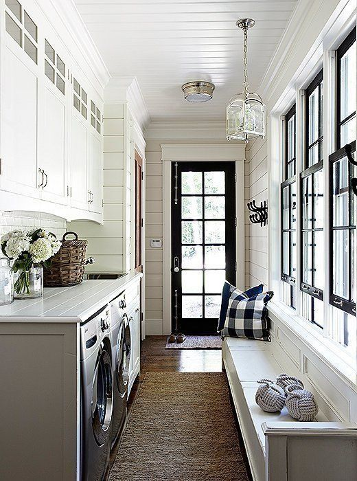Beautiful black and white entryway with laundry room, built-in bench and black window trim.