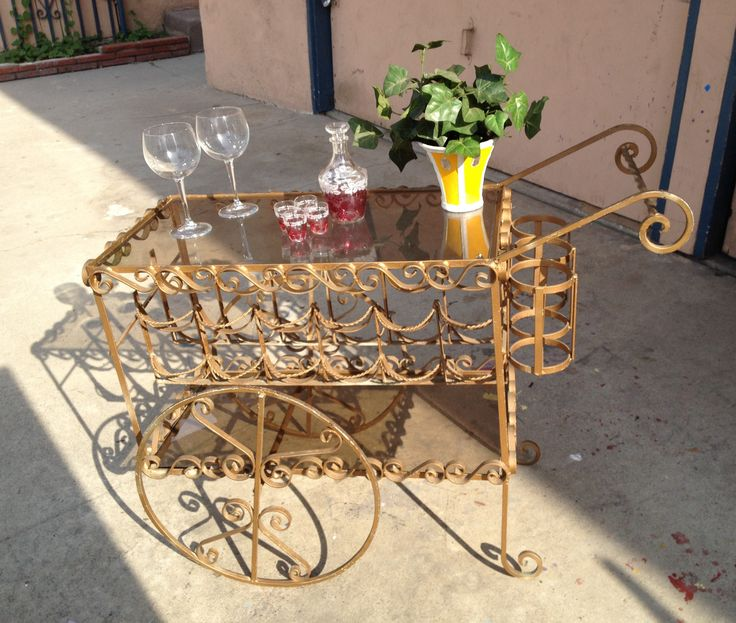 Charming and Romantic distressed wrought iron wine cart finished in gold with glass table top and moveable wheels.  $399.  New Vintage by Tosh