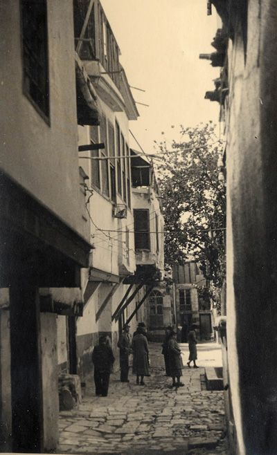 Photograph of British visitors to a narrow street in the old city of Damascus/Syria,taken in 1929 viewing the traditional architecture of the old charming homes,with first floors built of stone, and protruding second floors built of mud and supported by wooden posts.The streets are covered with cobble stones.