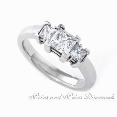 Centre stone is a 0.702ct  G – H/VS – SI Princess cut diamond with 2 side stones set in platinum